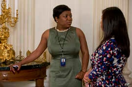 FILE - White House Social Secretary Deesha Dyer, left, talks with a colleague during the annual Mother's Day Tea hosted by first lady Michelle Obama and Jill Biden to honor military-connected mothers at the White House in Washington, May 8, 2015.