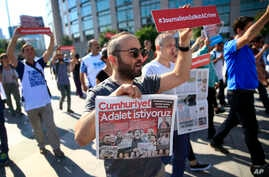 Activists, one holding today's copy of the Cumhuriyet newspaper, march to a court in Istanbul, July 24, 2017, protesting against the trial of journalists and staff from the newspaper, accused of aiding terror organizations.
