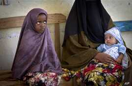 A Somali mother and her older child wait in line for her baby to receive a five-in-one vaccine against several potentially fatal childhood diseases, at the Medina Maternal Child Health center in Mogadishu, Somalia Wednesday, April 24, 2013. (AP Photo