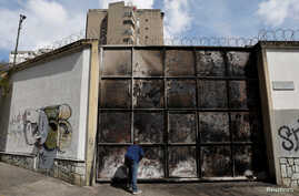 A resident looks at a burnt electrical substation after a massive blackout in Caracas, Venezuela, March 11, 2019.