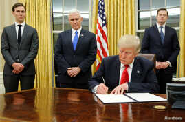 U.S. President Donald Trump, flanked by Senior Advisor Jared Kushner (standing, L-R), Vice President Mike Pence and Staff Secretary Rob Porter welcomes reporters into the Oval Office for him to sign his first executive orders at the White House in Wa