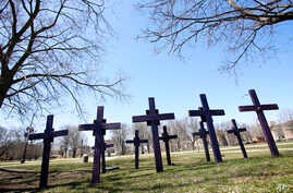 FILE - In this April 19, 2018 file photo, crosses representing victims of gun violence stand outside Collins Academy High School in Chicago's North Lawndale neighborhood.