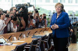 German Chancellor Angela Merkel, right, arrives for a news conference in Berlin Thursday, July 28, 2016.