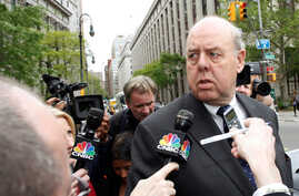 FILE - Lawyer John Dowd (R) is met with reporters as he exits Manhattan Federal Court in New York, NY, U.S., May 11, 2011.