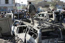 A Houthi fighter walks on a vehicle damaged by an air strike at a residential area near Sanaa Airport March 26, 2015. REUTERS/Khaled Abdullah