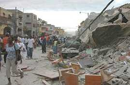 Haitians walk past damaged buildings in Port-au-Prince, 12 Jan 2010