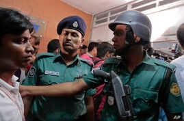 Bangladeshi policemen try to control the crowd of onlookers at a building where two people were found stabbed to death in Dhaka, Bangladesh, April 25, 2016.