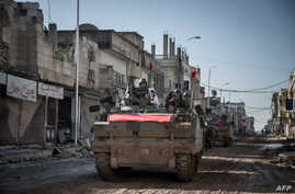 Turkish army vehicles drive in a street of the Syrian town of Kobani (aka Ain al-Arab), Feb, 22, 2015, during an operation to relieve the garrison guarding the Suleyman Shah mausoleum in northern Syria.