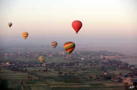 Hot air balloons fly over the west bank of the Nile River in Luxor, Egypt, April 1, 2016.