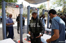 An Israeli border police officer asks to check the identity of a Palestinian man next to newly installed metal detectors at an entrance to the compound known to Muslims as Noble Sanctuary and to Jews as Temple Mount to be reopened, in Jerusalem's Old
