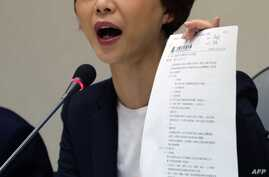 Chen Ting-fei, a lawmaker from the Democratic Progressive Party (DPP), displays a justice agreement signed between Taiwan and China to the press at Parliament in Taipei, April 12, 2016.