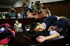 A student protester sleeps on the floor of the legislature after a night of scuffling with police in Taipei, Taiwan, Wednesday, March 19, 2014.