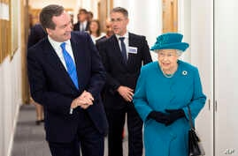 Britain's Queen Elizabeth II, right, walks with Director of GCHQ (Government Communications Headquarters) Robert Hannigan, during a visit to officially open the National Cyber Security Center (NCSC) in London, Feb. 14, 2017.
