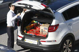 South Korean businessman with trunkload of Choco-pie snacks and noodles checks car before heading to the Kaesong Industrial Complex just north of the demilitarized zone separating the two Koreas, Sept. 16, 2013.