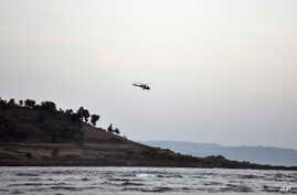 A helicopter on a search operation flies above the beach after more than a dozen college students were swept away at Murud on the Arabian Sea coast about 150 kilometers (95 miles) south of Mumbai, Maharashtra state, India, Monday, Feb. 1, 2016.