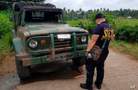 Police inspect a vehicle at a military checkpoint where a bomb exploded in Lamitan, Basilan province, southern Philippines, July 31, 2018.