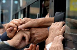 FILE - South Koreans and their North Korean relatives on a bus grip hands to bid farewell after the Separated Family Reunion Meeting at Diamond Mountain resort in North Korea, Oct. 22, 2015. Hundreds of elderly Koreans wept  and embraced as they part