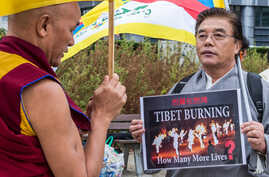 Member of the Tibetan Parliament in exile Thubten Wangchen, left, together with another protestor hold the Tibetan flag during the 'Flame of Truth' rally, near the European Commission headquarters in Brussels, September 20, 2012.