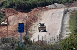 An Israeli bulldozer makes sand barriers on a road to an Israeli settlement, during a media trip organized by Hezbollah to show journalists the defensive measures established by the Israeli forces to prevent against any Hezbollah infiltration into Is...