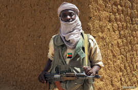 A fighter with the Tuareg separatist group MNLA (National Movement for the Liberation of Azawad) stands guard outside the local regional assembly, where members of the rebel group met with the Malian army, the UN mission in Mali and French army offic