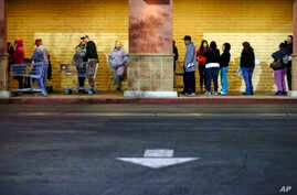 Shoppers wait outside a Kmart store for it to open on Thursday, Nov. 28, 2013, in Anaheim, California.