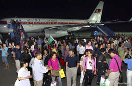 FILE - A group of tourists from Shanghai, China, arrive at an airport in Pyongyang in this picture taken on July 1, 2011.