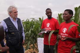 Beatrice Wisiki (R), a beneficiary of an EU-funded irrigation scheme in Zomba district, southern Malawi, tells EU commissioner Christos Stylianides about how she is benefiting from the project. (L. Masina/VOA)