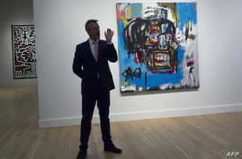 "A Sotheby's official speaks about ""Untitled,"" a 1982 painting by Jean-Michel Basquiat during a media preview at Sotheby's in New York, May 5, 2017. The work sold for $110.5 million Thursday in New York, setting a new auction record for the US artist"
