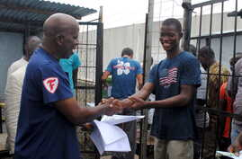 Cassius Kollie (R), 24, one of four people discharged on Monday from an Ebola treatment unit, receives a certificate for being cured of the disease in Paynesville, Liberia, July 20, 2015.