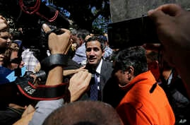 Supporters of opposition leader Juan Guaido and the press gather around him as he leaves a public plaza where he spoke in Caracas, Venezuela, Friday, Jan. 25, 2019.