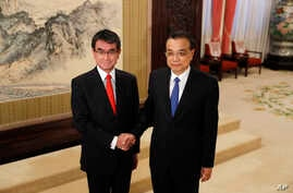 Japanese Foreign Minister Taro Kono, left, and Chinese Premier Li Keqiang pose for a photo before their meeting at the Zhongnanhai Leadership Compound in Beijing, Jan. 28, 2018.