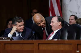 (L-R) Sen. Ted Cruz, R-Texas, Sen. Cory Booker, D-N.J., and Sen. Mike Lee, R-Utah, confer on the last day of the Senate Judiciary Committee's confirmation hearing for President Donald Trump's Supreme Court nominee, Brett Kavanaugh, on Capitol Hill in