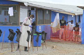 """FILE - Boys stand in the """"red zone"""" where they are being treated for Ebola at the Bong County ebola treatment unit about 200 km east of Monrovia, Liberia, Oct. 28, 2014."""