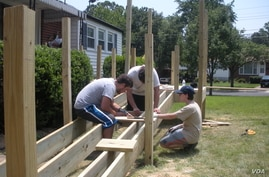 Yachad's teen volunteers build a wheelchair ramp at the New Carrollton, Maryland, home of Herson Portillo, 21, who has had cerebral palsy since birth. (Julie Taboh/VOA)