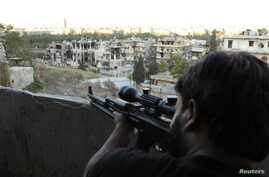 A Free Syrian Army fighter looks through the scope of his sniper rifle at an area controlled by forces loyal to Syria's President Bashar al-Assad in Aleppo's Al-Ezaa neighborhoo,d Sept. 11, 2013.