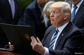 President Donald Trump prepares to sign the Executive Order on Promoting Free Speech and Religious Liberty during a National Day of Prayer event at the Rose Garden of the White House in Washington, May 4, 2017.