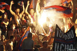 FILE - Russian soccer fans are seen chanting at a match at the Arena Khimki outside Moscow.