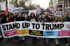 People hold a banner as they take part in a protest march in London, against U.S. President Donald Trump's ban on travelers and immigrants from seven predominantly Muslim countries entering the U.S., Feb. 4, 2017. Thousands of protesters marched on P