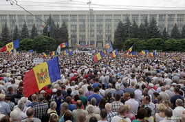 """Protesters carry Moldova's national flags during an anti-government rally, organised by the civic platform """"Dignity and Truth"""" (DA), in central Chisinau, Moldova, Sept. 6, 2015."""