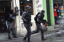 Policemen take position during an operation against drug gangs in the Alemao slums complex of Rio de Janeiro, Brazil Oct. 9, 2018.