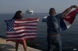 Yaney Cajigal, left, and Dalwin Valdes hold up U.S. and Cuban flags as they watch the arrival of Carnival's Adonia cruise ship from Miami, in Havana, Cuba, May 2, 2016.
