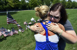 Sophia Ensley, left, comforts Barbie Branum by a makeshift memorial at the entrance to the Naval Operational Support Center and Marine Reserve Center in Chattanooga, Tennessee, July 18, 2015.