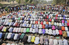 Muslims pray while Christians form a protective human chain around them during a protest on common problems faced in Nigeria, January 1, 2012.