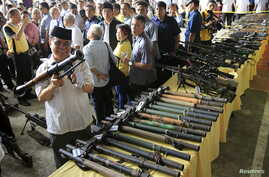 Philippine President Benigno Aquino (far L) talks to a religious leader while Al-haj Murad Ebrahim (2nd L), chairman of the Moro Islamic Liberation Front (MILF), inspects a B40 rocket launcher during the Ceremonial Turnover of Weapons and Decommissio...
