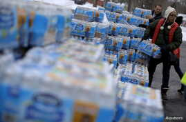 FILE - Volunteers distribute bottled water to residents in Flint, Michigan, March 5, 2016.