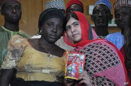 Pakistani activist Malala Yousafzai who survived being shot by the Taliban because she advocated education for girls, holds a picture of kidnapped schoolgirl Sarah Samuel with her mother Rebecca Samuel, during a visit to Abuja, Nigeria, July 13, 2014