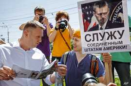 """Russian opposition activist and blogger Alexei Navalny, left, speaks to activists of a National Liberation movement holding a poster with a portrait of him and words reading """"Serve United States of America"""" during his visit in Novosibirsk, Russia, Su"""