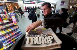 A man reaches for the New York Post newspaper featuring president-elect Donald Trump's victory, Nov. 9, 2016 in New York.