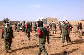 Soldiers attend to wounded and casualties in the aftermath of a suicide bomb attack who ripped through a camp grouping former rebels and pro-government militia in troubled northern Mali left 40 people dead on Jan. 18, 2017 in Gao.