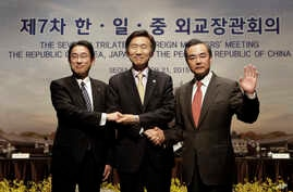 From right, Chinese Foreign Minister Wang Yi, South Korean Foreign Minister Yun Byung-se and Japanese Foreign Minister Fumio Kishida pose during the 7th trilateral foreign ministers' meeting in Seoul, South Korea,  March 21, 2015.